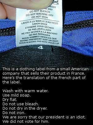 This is a clothing label from a small American company that sells their product in France. It reads: Laver à l'eau tiètde. Savon doux. Etendre pour sécher. Ne pas javelliser. Ne pas secher à la machine. Ne pas repasser. Nous sommes désol&eacutes que notre président soit un idiot. Nous n'avons pas voté pour lui.